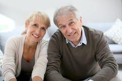 Lyckliga pensionärer hemma som kopplar av på soffan Royaltyfri Foto