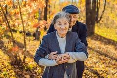 Lyckliga pensionärer i höstskogfamiljen, åldern, säsongen och folkbegreppet - lyckligt högt par som över går royaltyfri fotografi