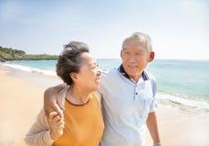 Lyckliga pensionärer som går på stranden arkivfoton