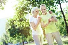 Lyckliga pensionärer som ser smartphonen arkivfoto