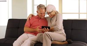 Lyckliga pensionärer som sitter på hållande ögonen på video för soffa på smartphonen arkivbilder