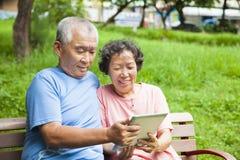 Lyckliga pensionärpar med minnestavlaPC Royaltyfri Fotografi