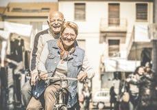 Lyckliga pensionerade höga par som har gyckel med cykeln på loppmarknaden royaltyfri foto