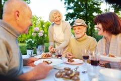 Lyckliga pensionärer på födelsedagpartiet med kakan Arkivbild