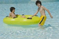 Lyckliga pojkar är i simbassängen Arkivbild