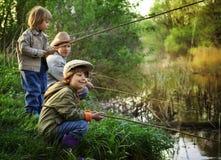 Lyckliga pojkar går att fiska Royaltyfri Bild