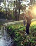 Lyckliga pojkar går att fiska på floden Royaltyfri Fotografi