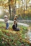 Lyckliga pojkar går att fiska på floden Royaltyfria Foton