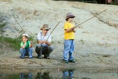 Lyckliga pojkar går att fiska på floden Arkivfoton