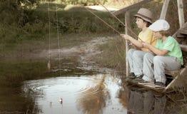 Lyckliga pojkar går att fiska på floden, två barn av fisheren med en metspö på kusten av sjön som är retro redigerar arkivbilder