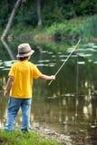 Lyckliga pojkar går att fiska på floden, två barn av fisheren w Royaltyfria Foton