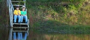 Lyckliga pojkar går att fiska på floden, två barn av fisheren w Arkivbild