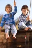 Lyckliga pojkar går att fiska på floden, två barn av fisheren w Royaltyfri Foto