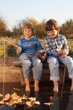 Lyckliga pojkar går att fiska på floden, två barn av fisheren w Fotografering för Bildbyråer