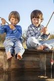 Lyckliga pojkar går att fiska på floden, två barn av fisherm Arkivfoto