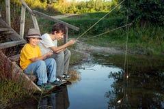 Lyckliga pojkar går att fiska på floden, två barn av fishermaen Royaltyfria Foton