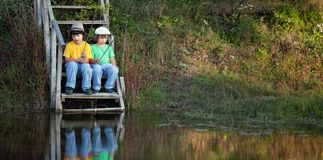 Lyckliga pojkar går att fiska på floden, två barn av fishermaen Arkivfoton