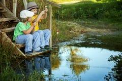 Lyckliga pojkar går att fiska på floden, två barn av fishermaen Royaltyfri Foto