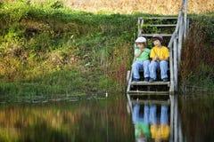 Lyckliga pojkar går att fiska på floden, två barn av fishermaen Royaltyfri Fotografi