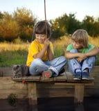 Lyckliga pojkar går att fiska på floden, två barn av fishermaen Royaltyfria Bilder