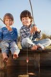Lyckliga pojkar går att fiska på floden, två barn av fishermaen Arkivbild