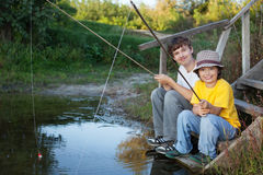 Lyckliga pojkar går att fiska på floden, två barn av fishermaen Arkivfoto