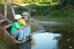 Lyckliga pojkar går att fiska på floden, två barn av fishermaen Royaltyfri Bild