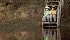 Lyckliga pojkar går att fiska på floden, två barn av fiskaren med en metspö på kusten av sjön royaltyfria bilder