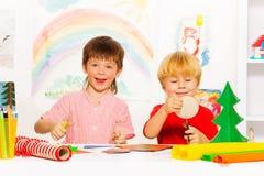 Lyckliga pojkar gör Xmas-garneringar med sax royaltyfria bilder