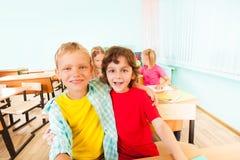 Lyckliga pojkar kramar och sitter tillsammans i klassrum Arkivbilder