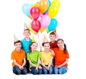 Lyckliga pojkar och flickor med kulöra ballonger Arkivbilder