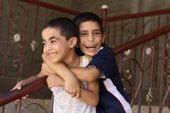 Lyckliga pojkar som leker i gatan i giza, egypt Arkivfoton