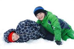 Lyckliga pojkar som spelar på en vinter, går i natur Barn som hoppar och har gyckel i vinter, parkerar royaltyfri bild