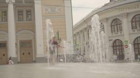 Lyckliga pojkar spelar i springbrunn nära Gostinniyen Dvor i Moskva stock video
