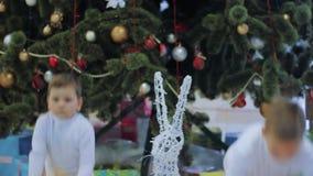 Lyckliga pojkar visar gåvor för ` s för det nya året Ungar som står under julgranen lager videofilmer