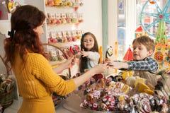 Lyckliga pojke- och flickaköpandesötsaker i lagret Royaltyfri Bild