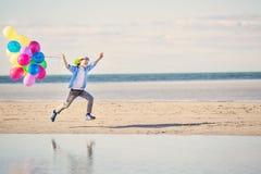 Lyckliga pojkelekar med kulöra ballonger på stranden Royaltyfri Bild