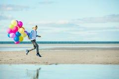 Lyckliga pojkelekar med kulöra ballonger på stranden Royaltyfri Fotografi