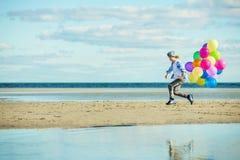 Lyckliga pojkelekar med kulöra ballonger på stranden Arkivfoto