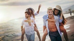 Lyckliga pojkv?nner som piggybacking deras flickv?nner p? stranden arkivfoto