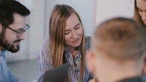 Lyckliga positiva le aff?rspartners som diskuterar arbete som ler p? id?kl?ckning p? kontorstabellen sund arbetsplats stock video
