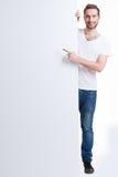 Lyckliga punkter för ung man fingrar på ett tomt baner. arkivfoton
