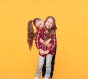 Lyckliga roliga flickasystrar som kramar och skrattar arkivbilder