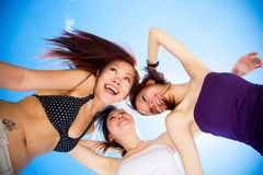 lyckliga roliga flickor för blåa ljusa vänner ha skyen under Arkivfoto