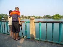 Lyckliga romantiska höga asiatiska par står på bron framme av sjön Maken står med hans fru Begrepp av hög coupl fotografering för bildbyråer