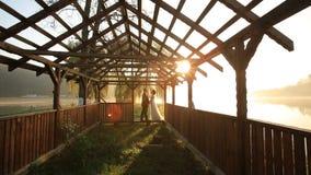 Lyckliga romantiska nygift personpar som kysser i strand, utgjuter dörröppningen på aftonen av bröllopdagen nära sjön för bergsem stock video