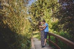 Lyckliga romantiska par i byn, promenad på träbron Ung härlig kvinna och man som kramar sig Royaltyfri Foto