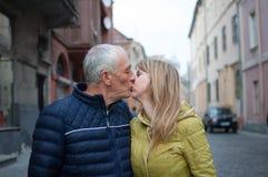 Lyckliga romantiska par med ?lderskillnaden som utomhus kysser i den forntida staden under den tidig v?ren eller h?st arkivbild