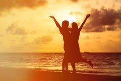 Lyckliga romantiska par på stranden på solnedgången Fotografering för Bildbyråer