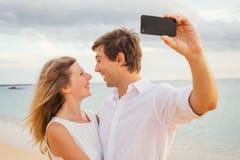 Lyckliga romantiska par på stranden som tar fotoet royaltyfria bilder